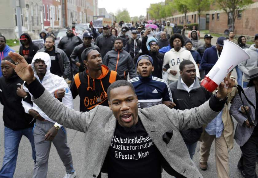 The Rev. Westley West leads a march for Freddie Gray to the Baltimore Police Department's Western District police station, Wednesday, April 22, 2015, in Baltimore. Gray died from spinal injuries about a week after he was arrested and transported in a police van. (AP Photo/Patrick Semansky)